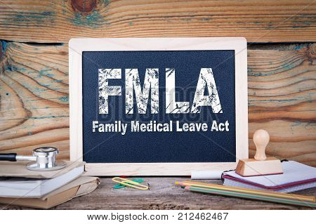 fmla, family medical leave act. Chalkboard on a wooden background.