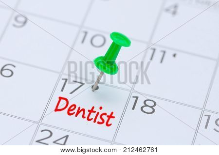 Dentist written on a calendar with a green push pin to remind you and important appointment.