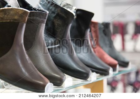 Men's winter boots. Men's winter boots in clothing store with selective focus.