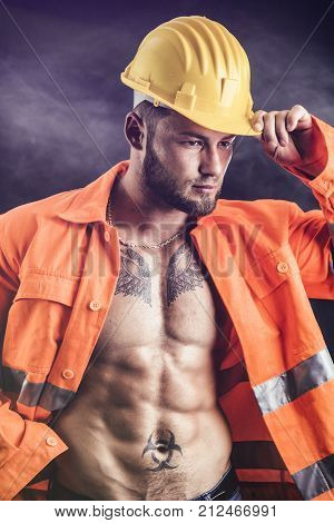Handsome sexy construction worker with orange suit open on naked torso, wearing yellow hardhat