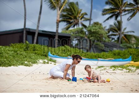 Young mother playing with her son on a tropical beach