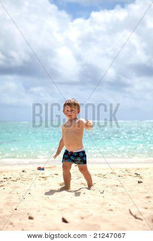 Cute toddler walking on a tropical beach