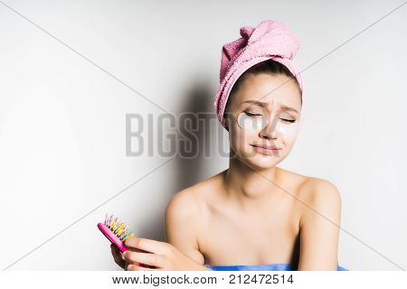 the girl after the shower with a pink towel on her head with patches on her face pulls out the hair from the comb and twists the face