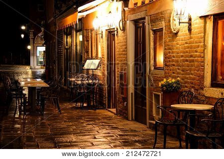 An outdoor café in Venice at night after the rain