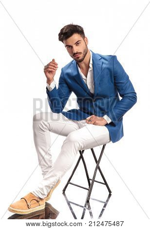 seated fashion model is posing for the camera on white background