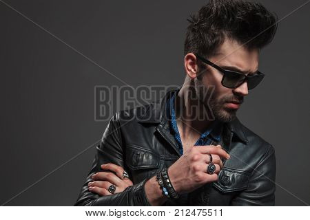 young hipster wearing rings, sunglasses and leather jacket looks down at something on grey background