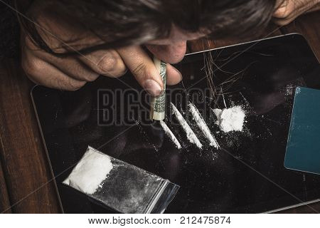 Drug abuse, man taking or sniffing drugs, snorting cocaine, top view