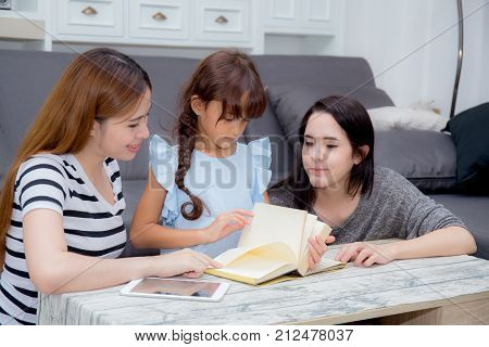 happy family mother aunt freind and daughter teaching read a book at home.