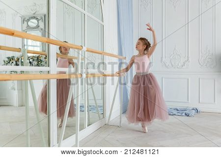 Young classical Ballet dancer side view. Beautiful graceful ballerine practice ballet positions in tutu skirt near large mirror in white light hall. Ballet class training, high-key soft toning.