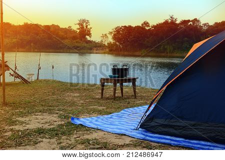 The Morning Atmosphere Of Camping. With Orange Sun Light ,fishing Rods, Tent And Food Pot