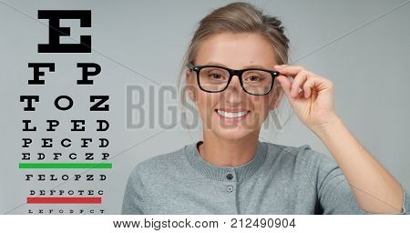 Eyesight Check. Woman In Glasses On The Background Of Eye Test Chart