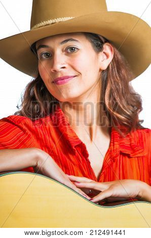 Pretty woman in a cowboy hat playing a guitar.