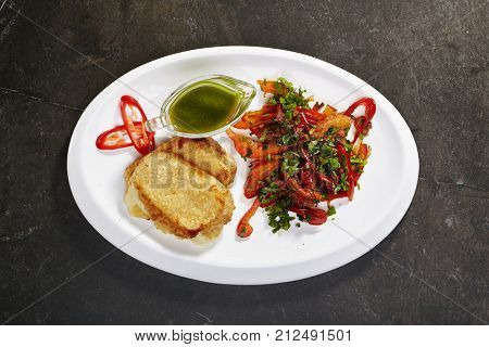 Fried suluguni cheese with spicy vegetables and pesto sauce with herbs and spicy peppers