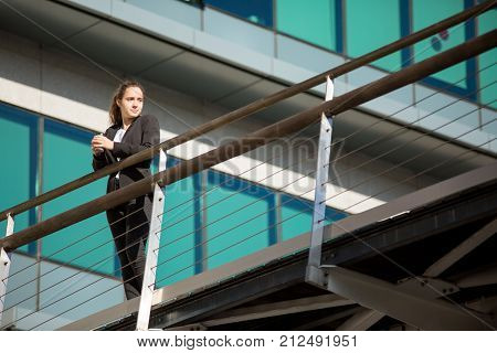 Ambitious young businesswoman relaxing after long day. Pensive attractive female employee leaning on railing and looking away. Dreams concept