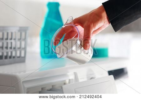 hand of woman that fills detergent from dosing cup in the washing machine