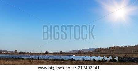 Arrangement of solar energy production plant. Solar collectors collect lass autumn sun rays in the field near the village in Germany. Ecology green energy and sustainable development.