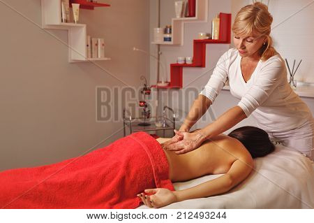 Spa treatment. Back massage. Massage of the zone of the waist. Moistening with oil. Restorative procedures
