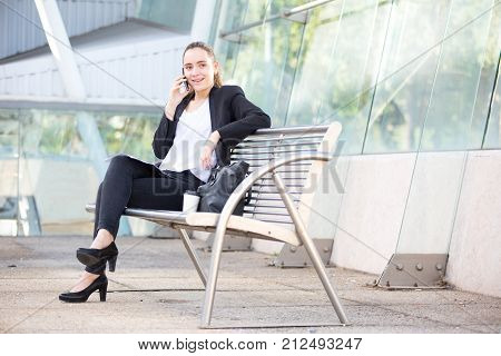 Thrilled young businesswoman talking to customer on phone and looking away. Positive busy lady solving work issue. Freelancer concept