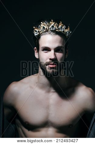 Freak gay and transvestite with naked chest. Man or prince in crown on grey background. Drag queen homosexual and trans. Fashion jewelry accessory. Glory nobility triumph concept.