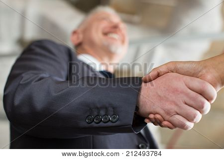 Closeup of smiling business man shaking partner hand with focus on hands. Partner is out of view. Low angle view.
