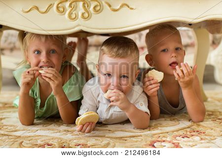 Closeup portrait of little girl and two boys looking at camera, eating cookies and lying under table at home. Front view.