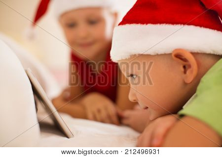 Curious boy in Santa hat watching with big interest cartoon on tablet. Smiling cute kid lying down and using modern device. Children and technology concept