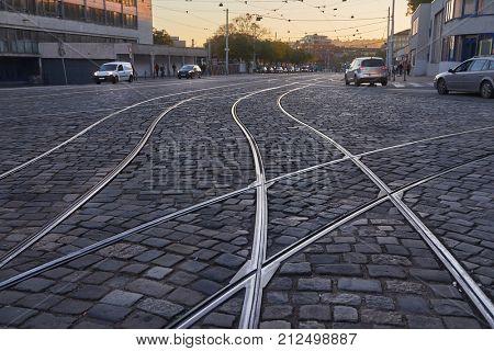 Tram rails rails through a cobblestone street