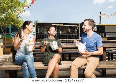 Three Friends Eating Oriental Food