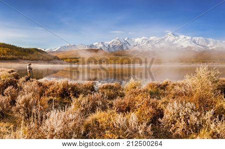 Male Photographer Taking Picture of Mountain Lake. Altai. Siberia.