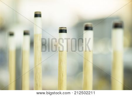 Billiard cues on the rack. Billiard game equipment. Wooden cues for table game. Billiard competition or championship. Cue stick shaft tapering with fiberglass. Maple wooden sticks for billiard playing