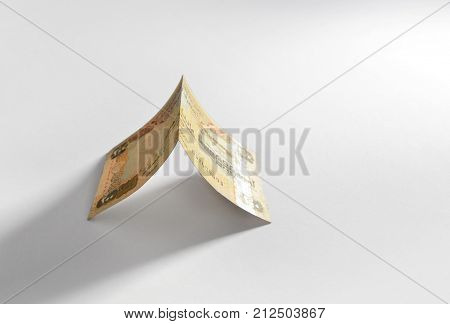 'Home' - an idea with currency note. Two hundred UAE dirham currency note is placed in a shape of tent. An idea.