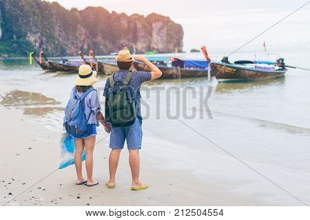 Young love couple traveler with backpack and hat holding map at the sea with long boat thailand background from Ao Nang Beach Krabi. Traveling in Krabi Thailand Traveler summer concept