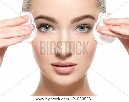 Girl removes makeup with cotton ball from face. Young woman cleans skin from cosmetic by cotton swab. Skin care concept.