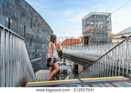 Vienna, Austria - August 17, 2017: Unidentified woman at Mumok Museum at sunset. It is a modern architecture building museum in the Museumsquartier with a collection of modern and contemporary art.