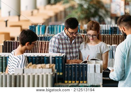 Young attractive students spending time in university library