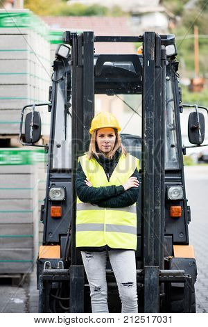Female forklift truck driver outside a warehouse. A woman standing in front of the fork lift truck, arms crossed.