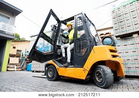 Female forklift truck driver outside a warehouse. A woman getting out of the fork lift truck.