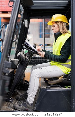 Female forklift truck driver outside a warehouse. A woman sitting in the fork lift making notes.