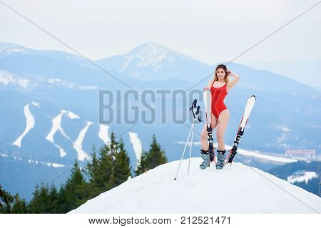 Female Skier Wearing Red Bodice, Resting With Skis And Poles On The Top Of The Slope. Winter Ski Res