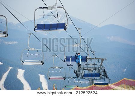 Happy Female Skier In Blue Ski Suit Sitting On A Cable Ski Lift With Skies At Winter Ski Resort, Wav