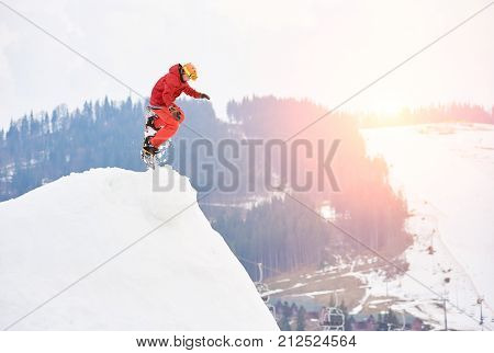 Man Snowboarder Jumping From The Top Of The Snowy Hill With Snowboard In The Evening At Sunset. Ski