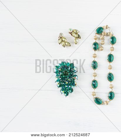 Woman's Jewellery. Vintage jewelry background. Beautiful bright rhinestone emerald brooch necklace and earrings on white. Flat lay top view.
