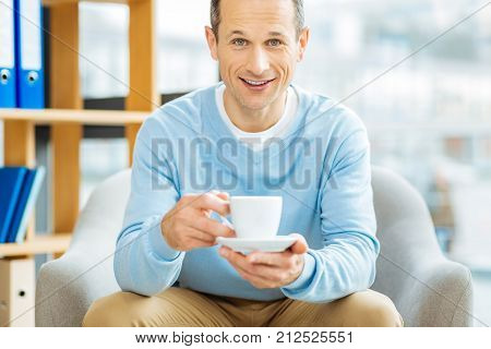 Positive emotions. Happy delighted joyful man holding a cup of coffee and smiling while being in a positive mood