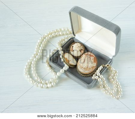 Woman's Jewelry. Vintage jewelry background. Beautiful pearl necklace bracelet and old cameos in a gift box on white wood. Flat lay top view.