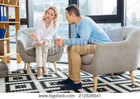My observations. Nice handsome professional therapist holding her notes and showing them to the patient while explaining the diagnosis