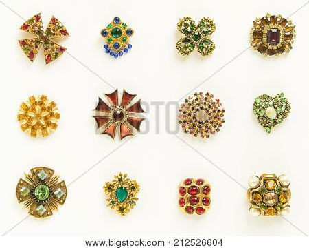 Woman's Jewellery. Old vintage brooches. Beautiful bright rhinestones brooches on white. Not isolated. Flat lay top view.