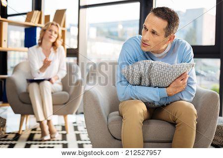 Feeling unsafe. Unhappy cheerless depressed man holding a pillow and hugging it while feeling unsafe