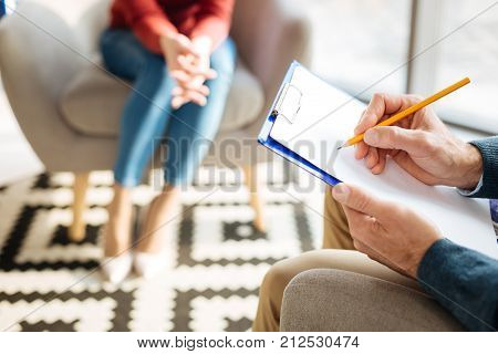 Doctors notes. Close up of a pencil being in hands of a smart professional male psychologist while being ready to take notes