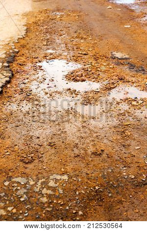 Bad Road. Pits, Potholes And Puddles After Rain On Paved Road. Background Is An Old Road With Cracke