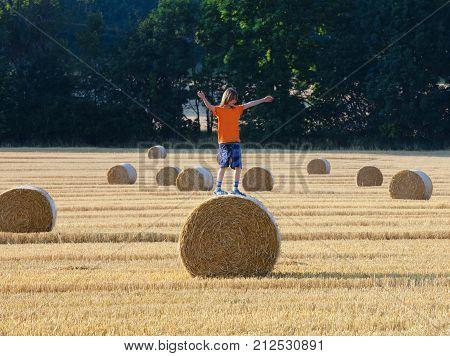 Boy Climbing a Bale of Hay on a Field in Summer